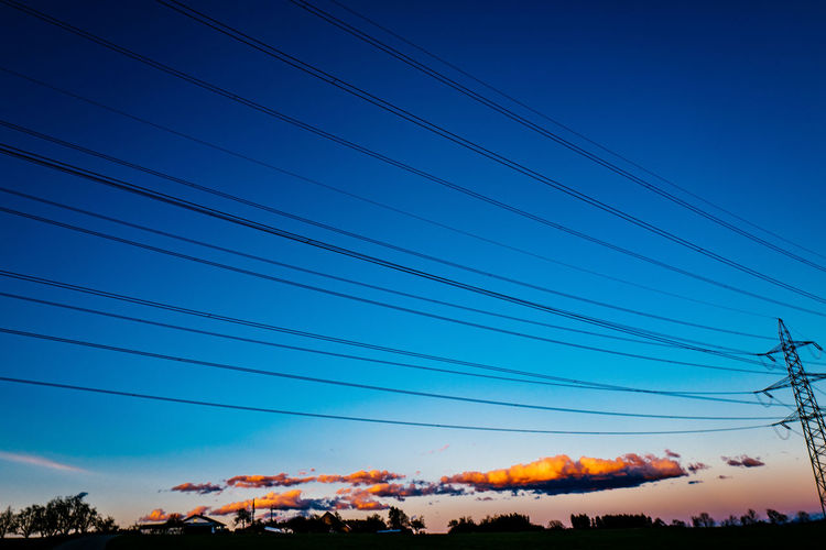 Beauty In Nature Blue Cable Clear Sky Connection Electricity Pylon Gormund Kapelle Landscape Low Angle View Nature No People Orange Color Outdoors Power Line  Scenics Silhouette Sky Sunset Tranquil Scene Tranquility Tree
