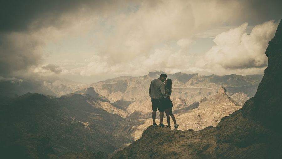 Couple kissing while standing against mountain range