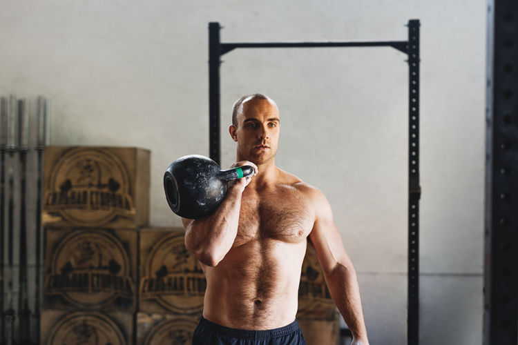 Shirtless Young Man Exercising With Kettlebell In Gym