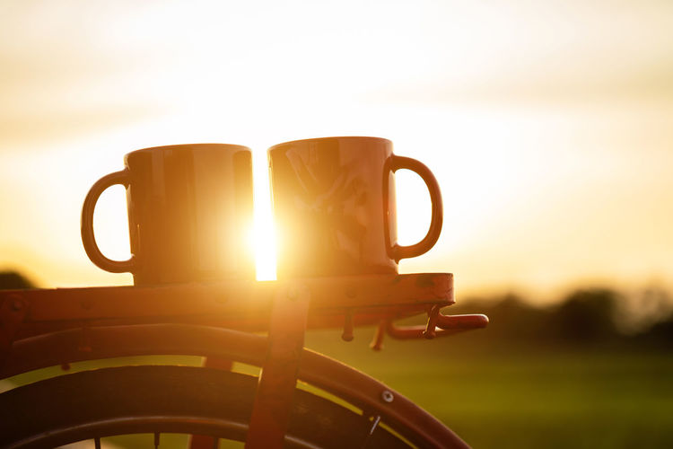 Close-up of coffee cup against sky during sunset