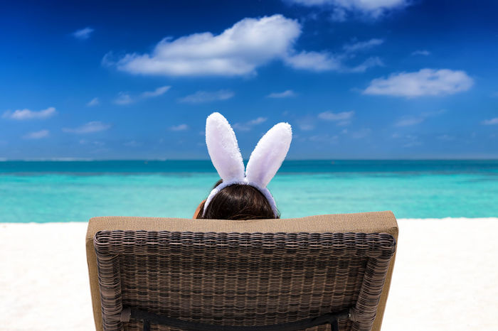 Woman with easter bunny ears relaxes on a sunbed on a tropical beach Easter Holiday Maldives Tropics Woman Beach Blue Bunny  Caribbean Day Ears Leisure Activity Lifestyles One Person Rear View Relaxation Sand Scenics Sea Sky Sunbed Sunchair Vacation Vacations Water