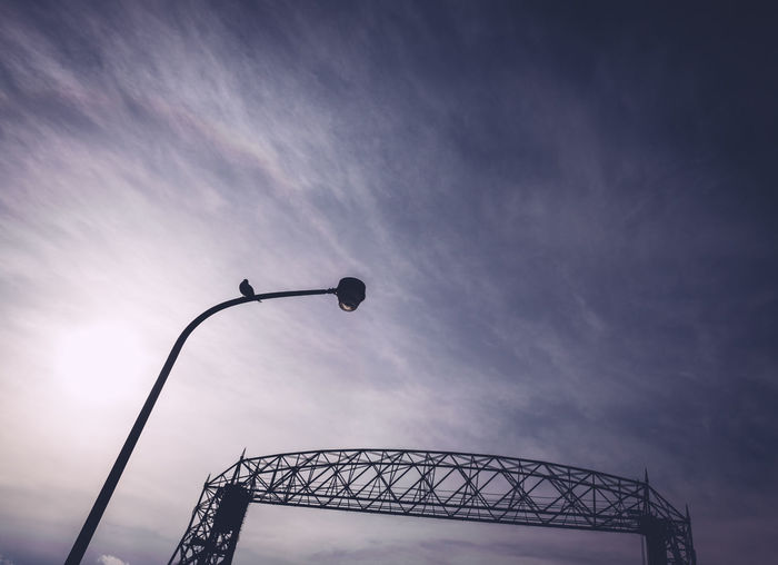 Low angle view of street light and structure against sky during sunset