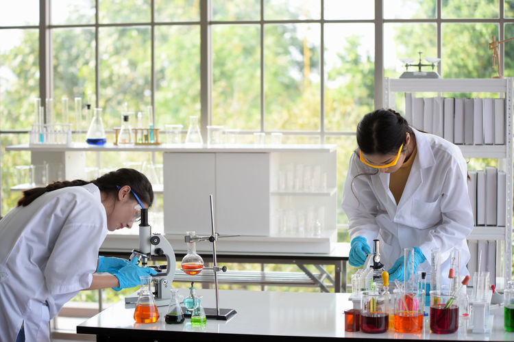 Women experimenting chemicals in laboratory