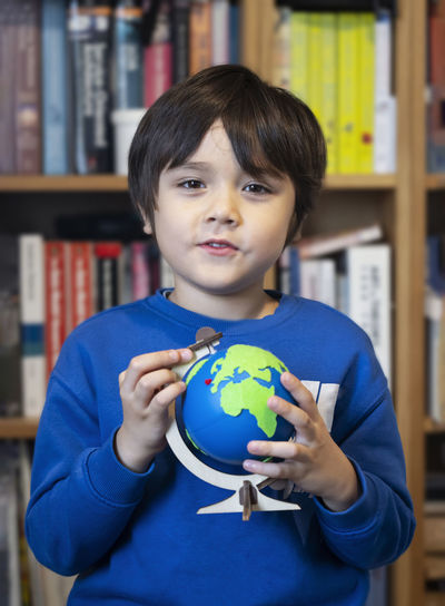 Portrait of boy holding globe against bookshelf