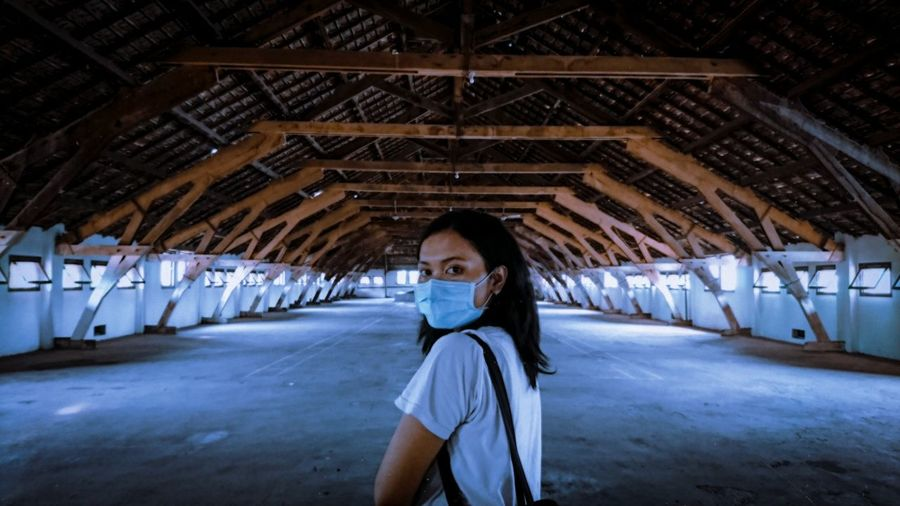 Portrait of woman wearing face mask standing in empty warehouse