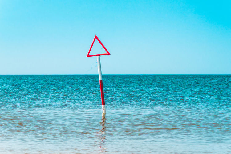 Blue Clear Sky Communication Day Horizon Horizon Over Water Nature No People Outdoors Road Sign Sea Shape Sign Sky Tranquil Scene Tranquility Triangle Shape Warning Sign Water