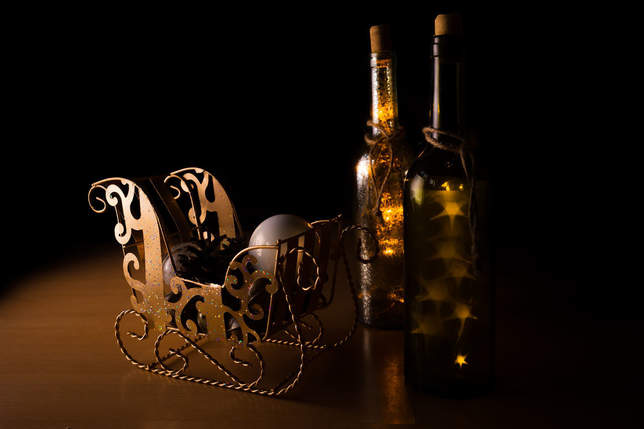 indoors, still life, bottle, studio shot, glass - material, container, black background, no people, table, close-up, alcohol, transparent, food and drink, illuminated, glass, drink, copy space, refreshment, dark, reflection