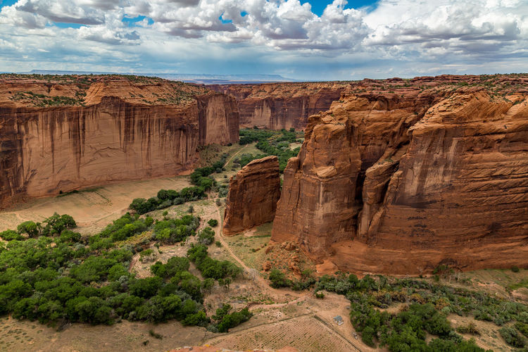 The Canyon de Chelly National Monument consists of many well-preserved Anasazi ruins and spectacular sheer red cliffs that rise up to 1000 feet. Arizona Beauty In Nature Canyon Canyon De Chelly National Monument Cliff Cloud - Sky Desert Dry Environment Eroded Geology Landscape Limestone No People Outdoors Ravine Red Rock - Object Rock Formation Sandstone Scenics Tourism Travel Travel Destinations Vibrant Color