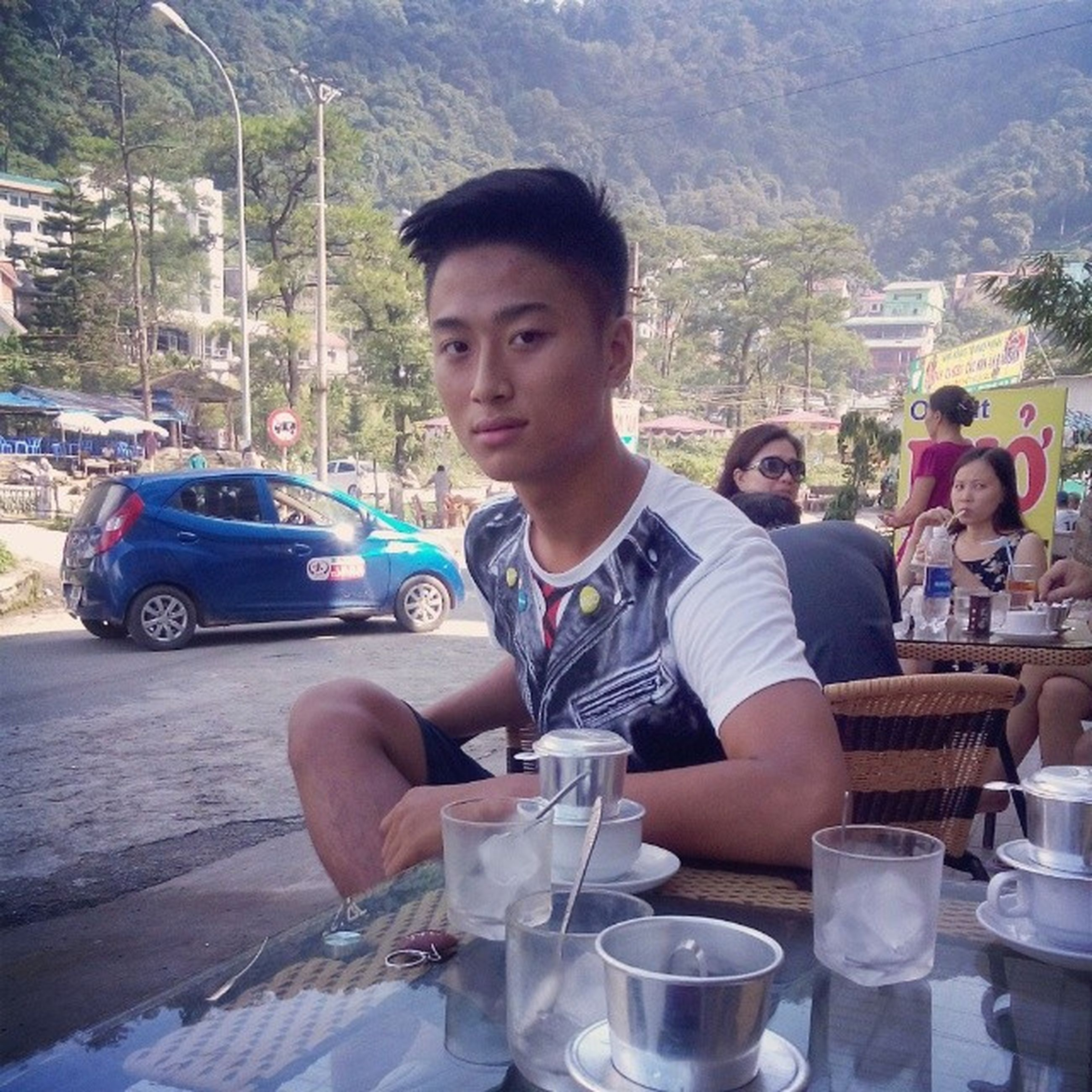 lifestyles, sitting, casual clothing, leisure activity, person, food and drink, looking at camera, young men, young adult, front view, portrait, table, holding, smiling, food, incidental people, drink, sunglasses