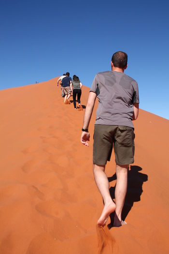 Rear view of man walking on desert against clear sky