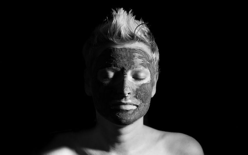Shirtless woman wearing mask against black background