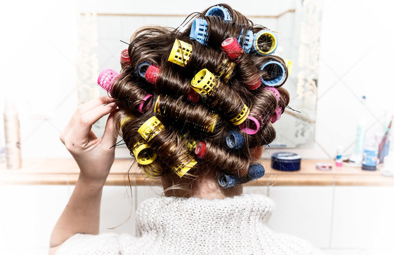 Rear view of woman with curlers in hair