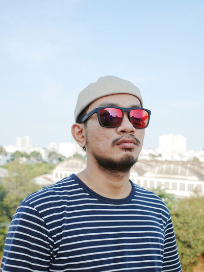 Portrait of young man wearing sunglasses against sky
