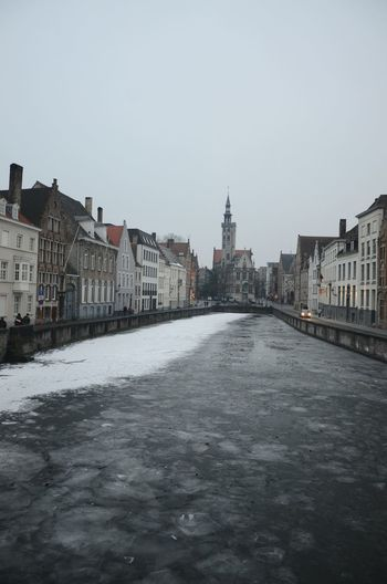 River in city against clear sky during winter