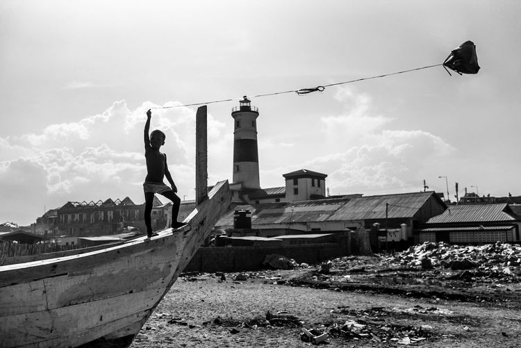 Shirtless boy holding kite while standing on boat against sky