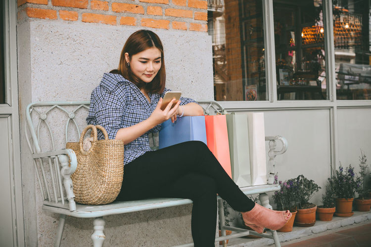 Woman using phone while sitting on bench