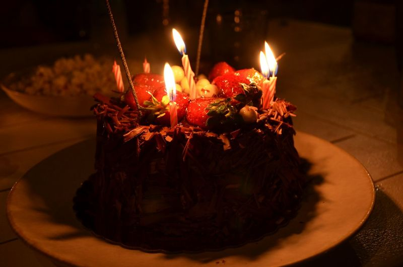 Close-Up Of Candles Burning On Birthday Cake In Darkroom