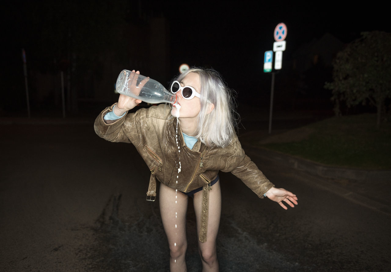 Young woman drinking water while standing on road at night