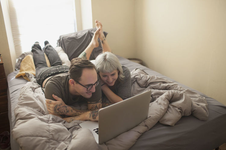 Midsection of woman using mobile phone while relaxing on bed at home