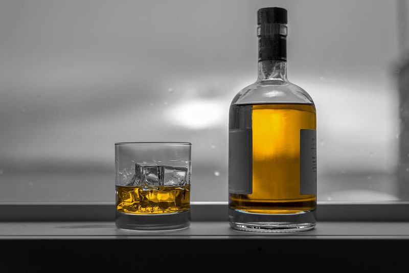 Expensive bottle of amber alcohol with ice on window sill selective color. Alcohol Amber Bottle Bourbon Dram Drinking Entertaining Expensive Glass House Ice Lake Lifestyle Liquid Liquor Malt Masculine Rocks Scotch Sea Selective Color Success Wealth Whiskey Window