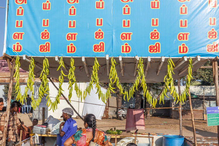 Local food stall selling chilly pakodas and green chilies are made to hang like a chain Business Chily Sale Adult Architecture Building Exterior Clock Communication Day Food Freshness Hanging Large Group Of Objects Men Outdoors Pakoda People Real People Stall Text