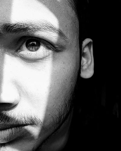Cropped Eye Of Young Man Against Black Background