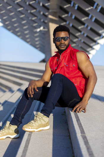 Front view of young black man wearing sunglasses sitting on staircase in a sunny day while looking away Glasses Looking At Camera Portrait Front View Sunglasses Full Length Fashion One Person Real People Leisure Activity Day Lifestyles Architecture Young Men Casual Clothing Sunlight Young Adult Smiling Men Outdoors African American Looking At Camera Sleeveless  Sitting Staircase Stairs Sunlight Daylight Muscular Build Wellbeing