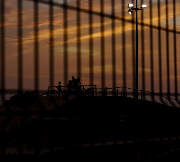 Silhouette Family At Skateboard Park Seen Through Fence Against Sky During Sunset