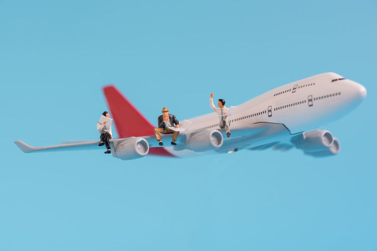 Close-up of male figurines sitting on model airplane against blue background