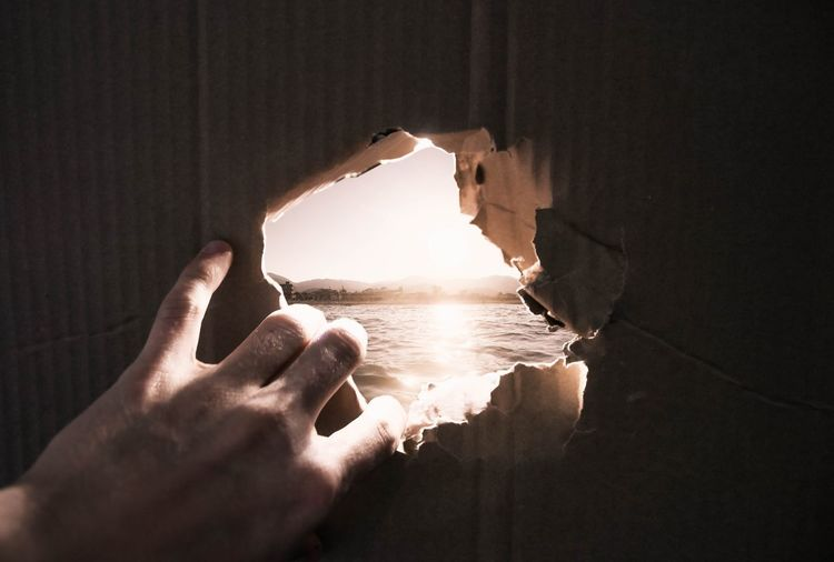 Close-up of hand tearing cardboard against sea during sunset