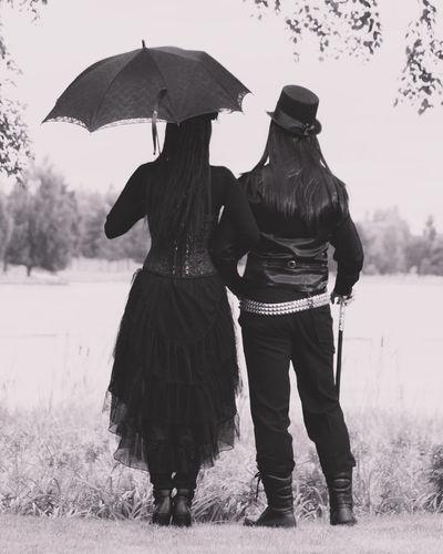 Rear view of women standing on grassy field