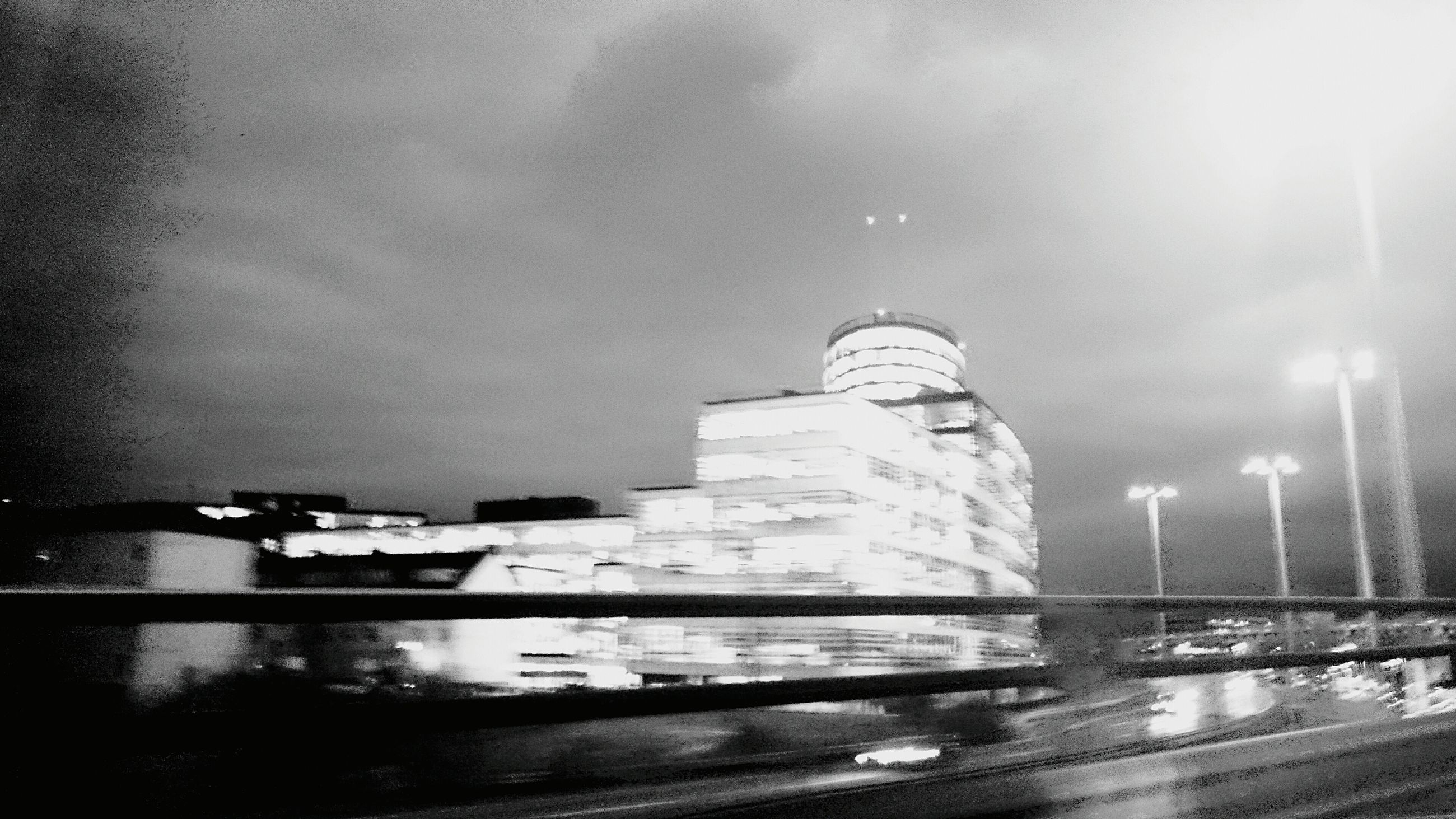 water, building exterior, sky, built structure, architecture, weather, transportation, night, mode of transport, car, wet, reflection, rain, street, city, outdoors, road, no people, land vehicle