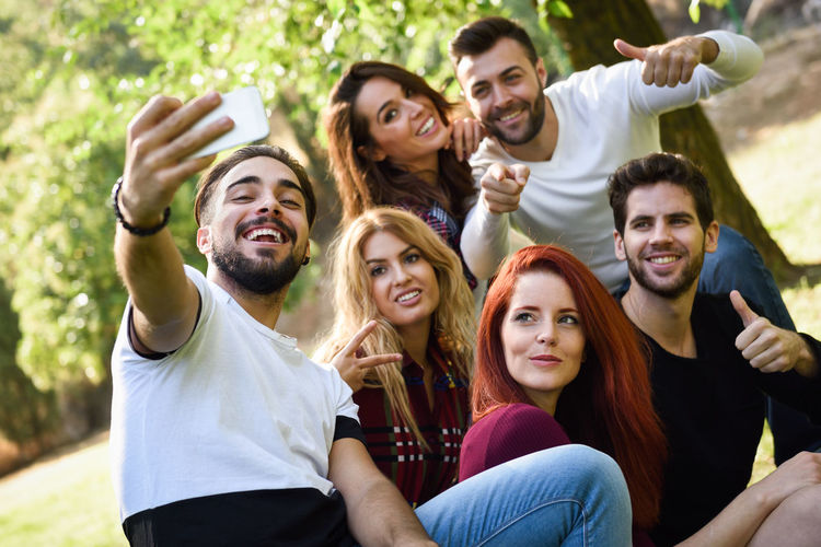 Group of friends taking selfie in urban park. Five young people wearing casual clothes. Cheerful Communication Friendship Fun Happiness Leisure Activity Lifestyles Mobile Phone Outdoors Photo Messaging Photographing Photography Themes Portable Information Device Portrait Real People Selfie Sitting Smart Phone Smiling Technology Togetherness Wireless Technology Young Adult Young Men Young Women