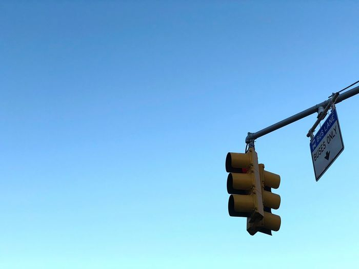 Low angle view of stoplight against clear blue sky