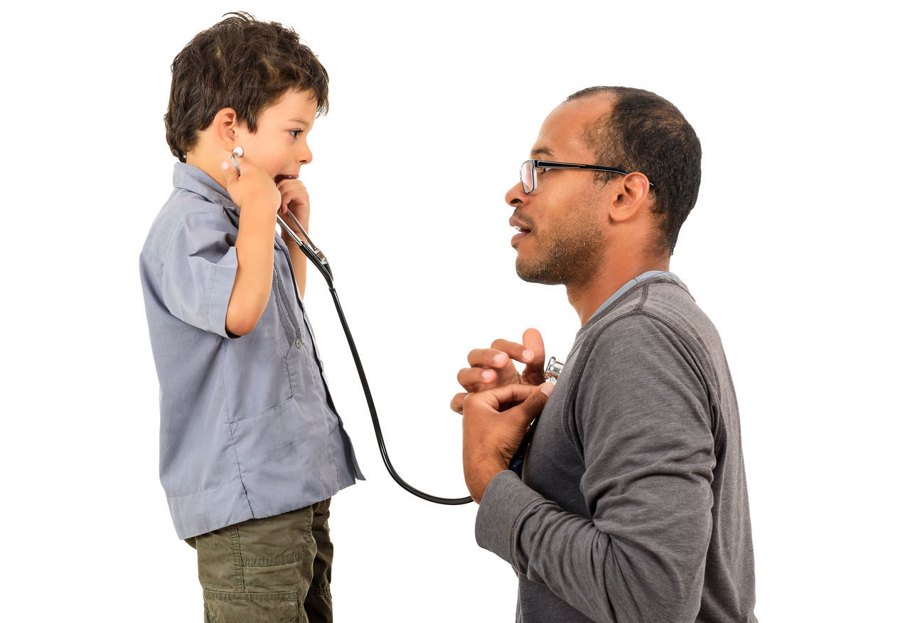 Boy Listening To Heartbeats Of Father While Standing Against White Background