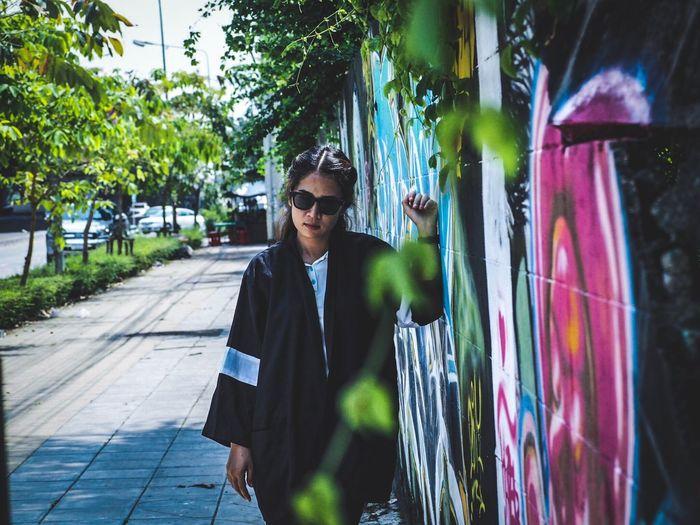 Woman standing by graffiti wall