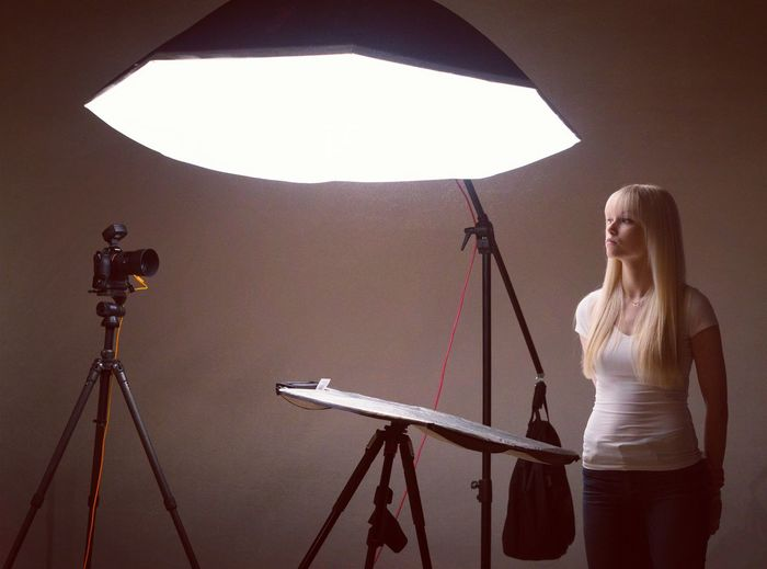 Woman photographing against gray background