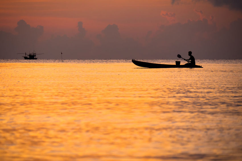 Fisherman in a canoe during sunset EyeEmNewHere Canoe Canoeing Thailand Beauty In Nature Canoe Paddling Fisherman Fisherman Boat Fishermen's Life Leisure Activity Nature Nautical Vessel One Person Orange Color Real People Scenics Silhouette Sunset Thailand Travel Transportation Water Waterfront