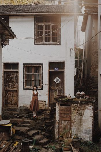 Woman standing by window of old building