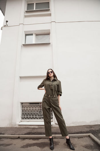 Female fashion model, posing for a full length photo, wearing green suit, urban fashion photography