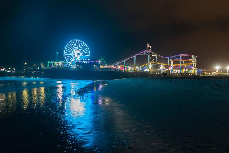 Illuminated ferris wheel by sea against sky at night
