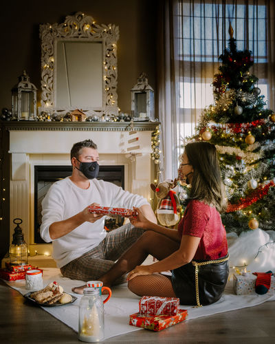 Woman wearing mask giving gift to man by christmas tree