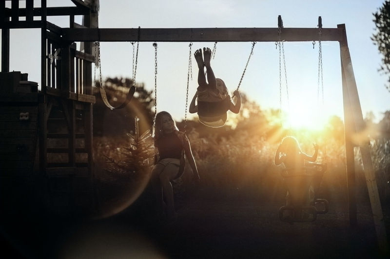People on swing in playground against sky