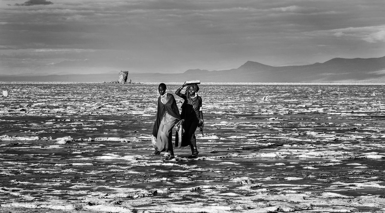 PEOPLE ON SHORE AGAINST SKY