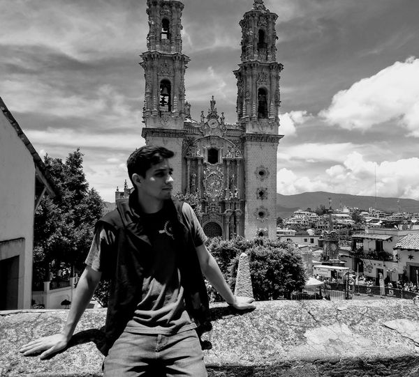 Young Man Sitting On Retaining Wall Against Santa Prisca Church During Sunny Day