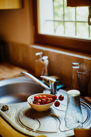 Tomatoes in bowl by sink at home