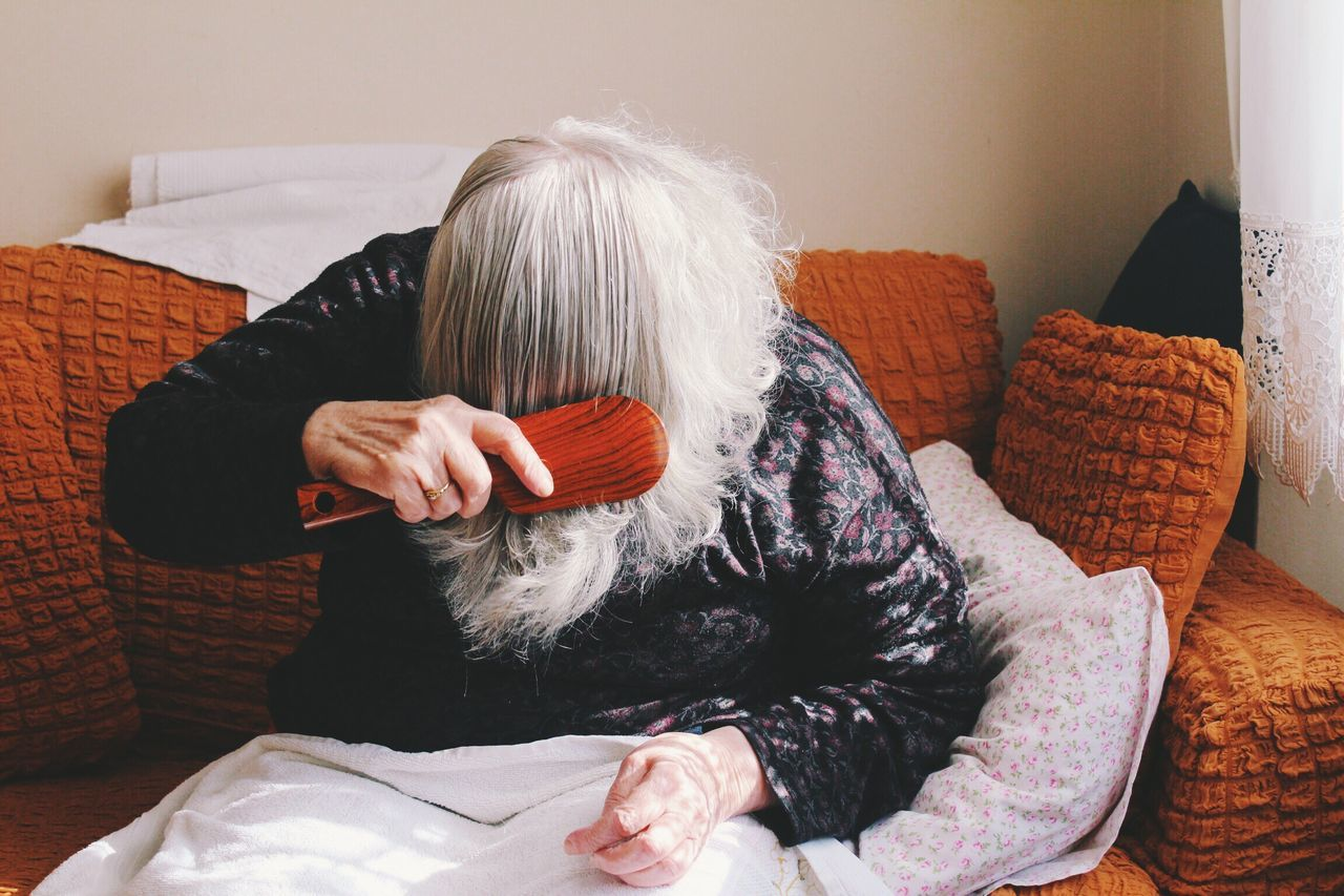 real people, sofa, indoors, senior women, one person, senior adult, women, leisure activity, lifestyles, sitting, casual clothing, bed, home interior, human hand, pillow, day, people