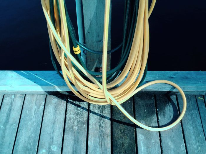 High angle view of garden hose on pier