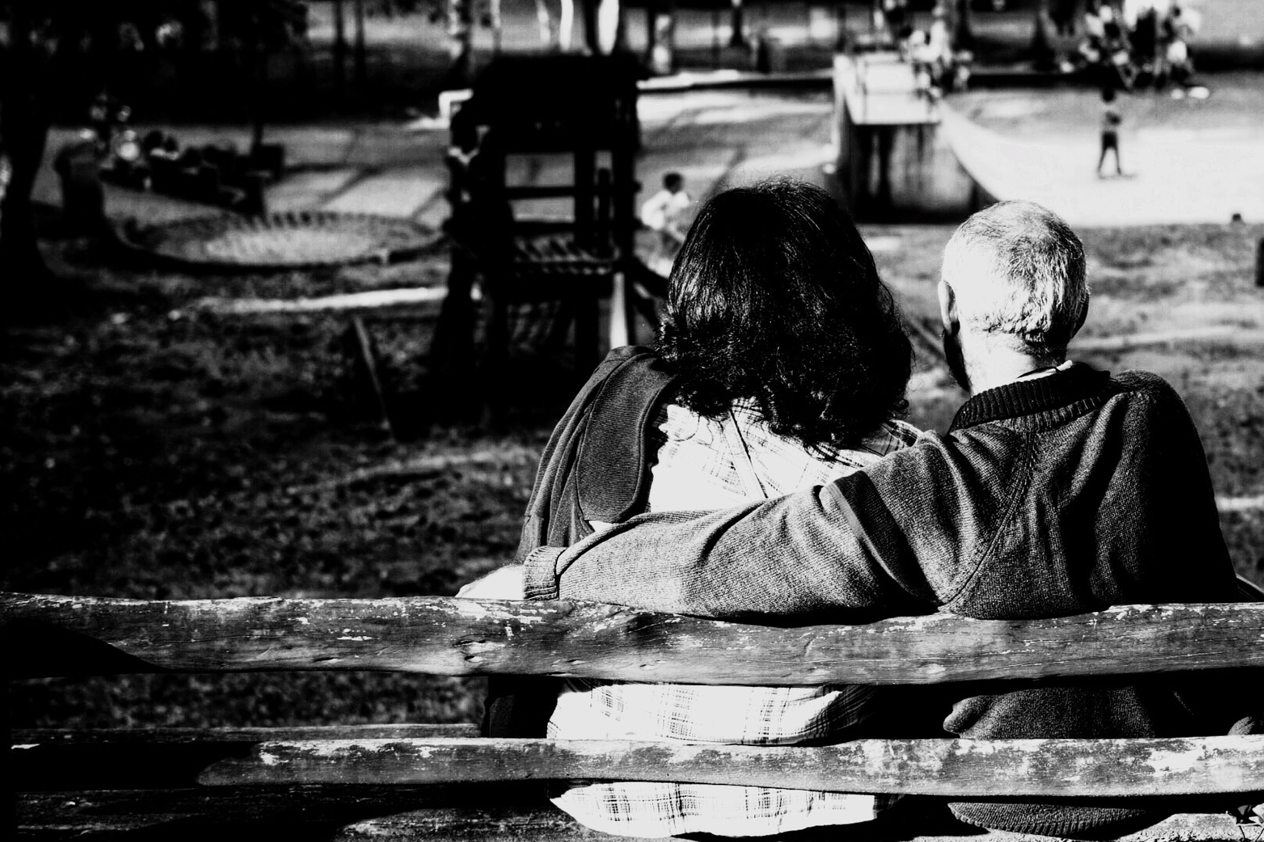 rear view, focus on foreground, sitting, full length, incidental people, childhood, day, water, lifestyles, bench, outdoors, street, leisure activity, tree, casual clothing, side view, relaxation, park - man made space