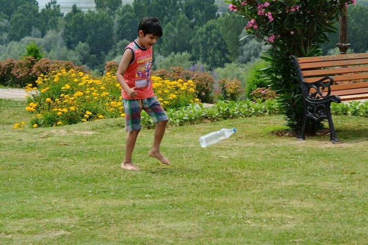 Full length of boy playing with bottle on field at park